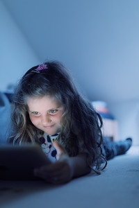 Little Girl watching movie On A Digital Tablet