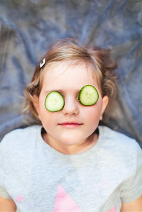 Funny small girl with piece of cucumber