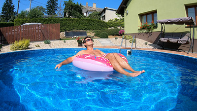 Happy man relax on inflatable ring. Holiday 2020