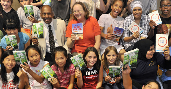 BUCKET - Dana Brooks, dean of the College of Physical Activity and Sport Sciences, and Frances O'Brien, dean of WVU Libraries, present books donated by WVU Libraries to participants in the National Youth Sports Program. (summer 2010)