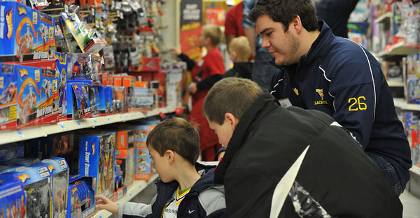 BUCKET: December 2010 - Lacrosse club team member with children participating in the SHOP (Students Helping Other People) program