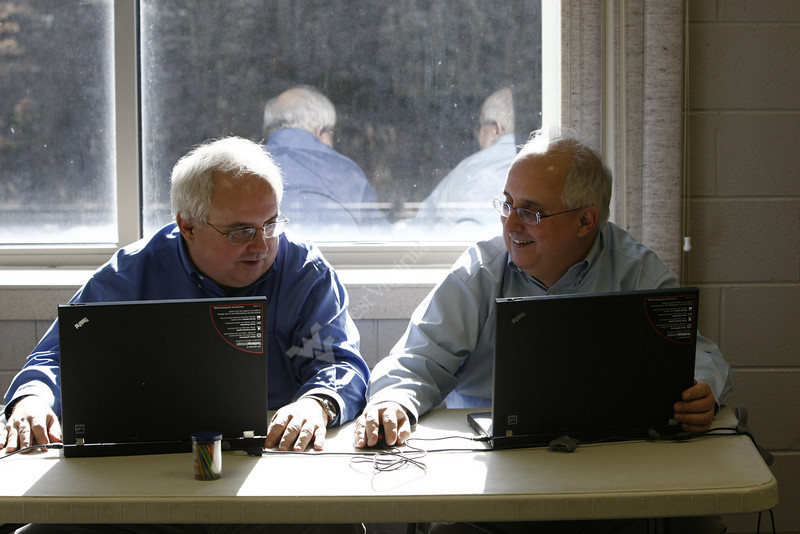 5/17  Doctors James, left, and John Brick hold their monthly medical clinic at the Larry Joe Harless Community Center in Gilbert, WV on 3/4/2010. The twin brothers are professors at WVU's Health Sciences Center; James in rheumatology and John in neurology.  This makeshift office is made up of curtains hanging on metal frames. Gilbert is a small town in Mingo County. Photo by Scott Lituchy/WVU