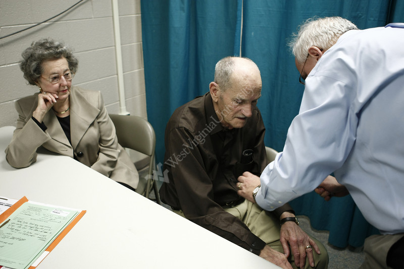 8/17  Dr. John Brick talks examines Elijah Winston Cline, of who is here with wife Faye Cline.   Elijah, of Gilbert, is having memory problems. Doctors James and John Brick hold their monthly medical clinic at the Larry Joe Harless Community Center in Gilbert, WV on 3/4/2010.The twin brothers are professors at WVU's Health Sciences Center; James in rheumatology and John in neurology.  This makeshift office is made up of curtains hanging on metal frames. Gilbert is a small town in Mingo County. Photo by Scott Lituchy/WVU
