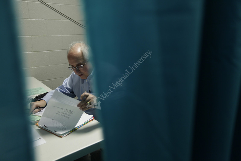 16/17  Dr. John Brick looks over a patient's file. Doctors James and John Brick hold their monthly medical clinic at the Larry Joe Harless Community Center in Gilbert, WV on 3/4/2010. The twin brothers are professors at WVU's Health Sciences Center; James in rheumatology and John in neurology. This makeshift office is made up of curtains hanging on metal frames. Gilbert is a small town in Mingo County. Photo by Scott Lituchy/WVU