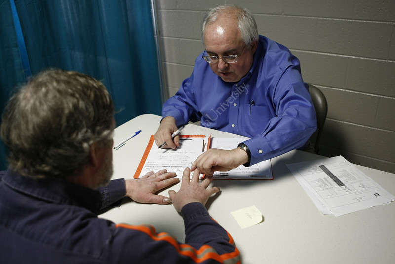 6/17  Dr. James Brick examines patient Stewart Johnson's hands. Johnson, of Wharncliffe, WV is a coal miner who has arthritis. Doctors James and John Brick hold their monthly medical clinic at the Larry Joe Harless Community Center in Gilbert, WV on 3/4/2010.The twin brothers are professors at WVU's Health Sciences Center; James in rheumatology and John in neurology. This makeshift office is made up of curtains hanging on metal frames. Gilbert is a small town in Mingo County. Photo by Scott Lituchy/WVU