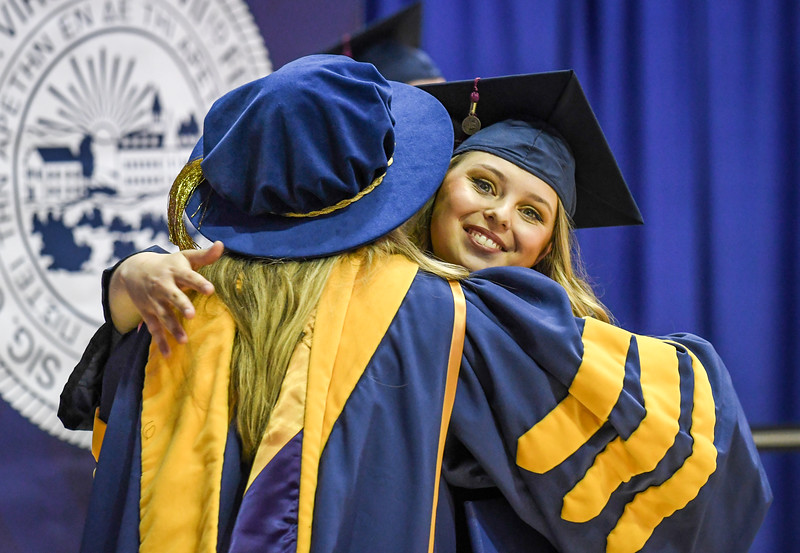 Hugs all around during Commencement, May 10, 2019. Photo: Geoff Coyle