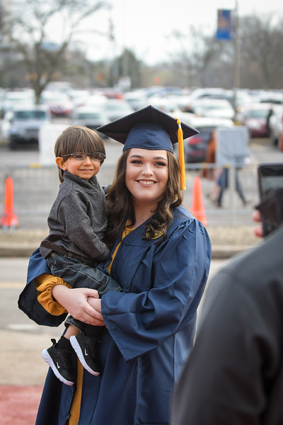 A WVU student smiles as she takes a photo with her younger brother following Commencement on Dec. 21, 2019. Photo: Geoff Coyle