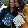 Two students pose for a picture with their graduation caps in Woodburn Circle on May 8, 2019. (Photo Chris Young)