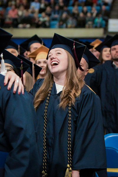 A WVU student smiles as she sings Country Roads at the conclusion of Commencement on Dec. 21, 2019. Photo: Geoff Coyle.