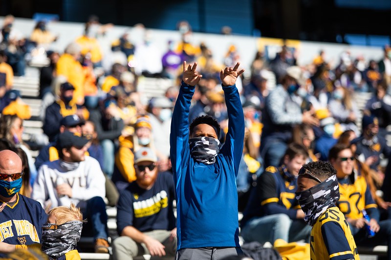 A young masked WVU fan cheers on the Mountaineers during their home game against Kansas State, Oct. 31, 2020. Photo: Corbin Mills