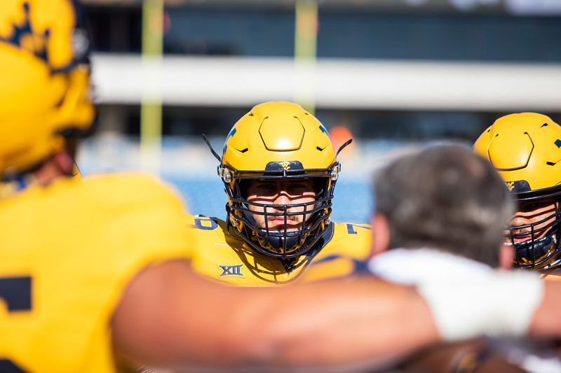 A WVU football player stands in a team huddle prior to WVU's home game against Kansas State, Oct. 31, 2020. Photo: Corbin Mills
