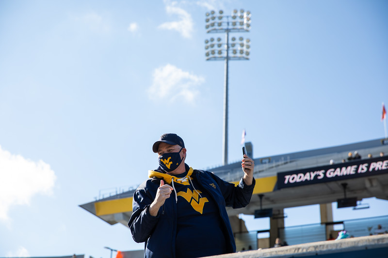 A masked WVU fan takes a selfie prior to WVU's home game against Kansas State, Oct. 31, 2020. Photo: Corbin Mills