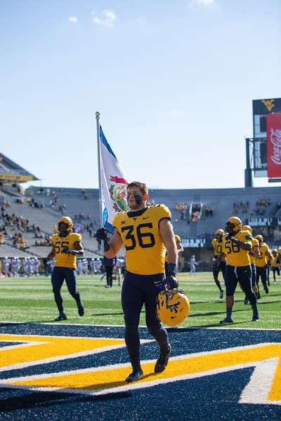 WVU football player Jake Abbott carries the West Virginia flag into the end zone prior to WVU's home game against Kansas State, Oct. 31, 2020. Photo: Corbin Mills