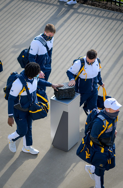 WVU football players touch a piece of coal on their way into Milan Puskar Stadium for a game against TCU, Nov. 14, 2020. Photo: Geoff Coyle