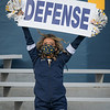 "A WVU cheerleader holds up a ""defense"" sign while rooting for the home team in a win over TCU, Nov. 14, 2020. Photo: Geoff Coyle"