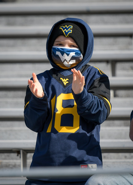 A young WVU fan claps for the Mountaineers during the first half of a win over TCU, Nov. 14, 2020. Photo: Geoff Coyle