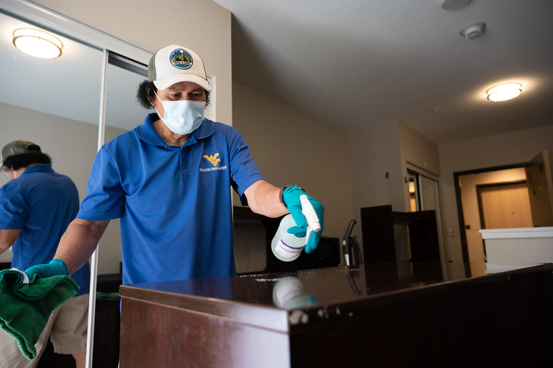 A WVU facilities employee disinfects a desk Oakland Hall during the Covid-19 Coronavirus global pandemic. (Photo Chris Young).