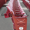A red stadium seat in detail with rows of seats blurred behind the main seat at a baseball stadium.