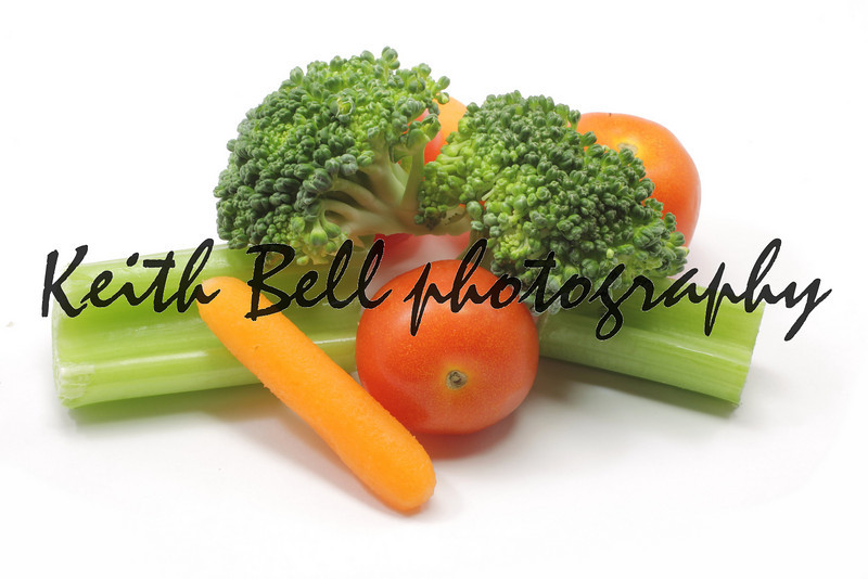 A healthy snack of carrots, celery, broccoli, and tomatoes.