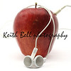 Red Delicious apple wrapped in music earbuds photographed on a white background