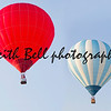 SEYMOUR, WI - AUGUST 3: A White and blue striped and a big red hot air balloon high in the sky flying together at the Balloon Rally at the Annual Hamburger Festival on August 3, 2012 in Seymour, Wisconsin.