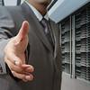 businessmen offer hand shake in a technology data center