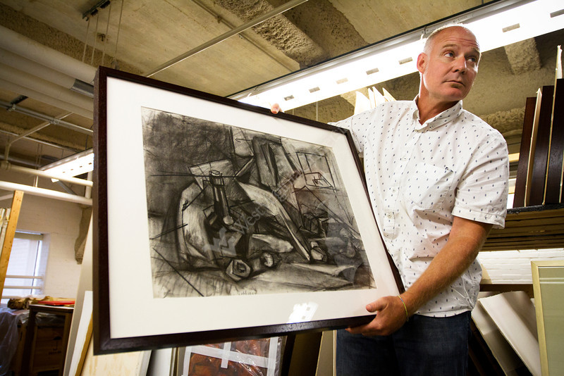 Robert Bridges, curator of the Art Museum of WVU, holds a piece by West Virginia artist Blanche Lazzell in the art storage area at the downtown library. Lazzell made the piece while studying under renowned artist Hans Hofmann.