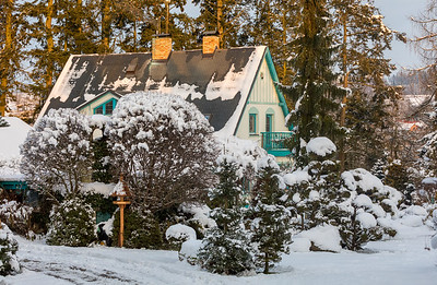 beautiful house in winter garden covered by snow