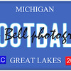 An imitation Michigan license plate with December 2014 stickers and FOOTBALL written on it making a great concept.  Words on the bottom Great Lakes.