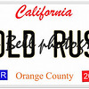 An imitation California license plate with April 2016 stickers and GOLD RUSH written on it making a concept.  Words on the bottom Orange County.