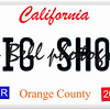An imitation California license plate with April 2016 stickers and BIG SHOT written on it making a concept.  Words on the bottom Orange County.