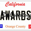 An imitation California license plate with April 2016 stickers and AWARDS written on it making a concept.  Words on the bottom Orange County.