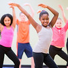 A diverse group of children learning choreography in a dance class.