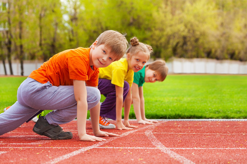 Two boys and girl stand on knee ready to run