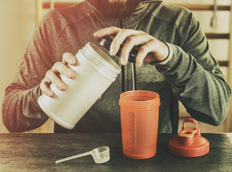 A woman mixing an elemental diet shake in her kitchen