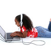 Adorable Six Year Old Girl Sitting On Floor With Laptop Computer And Headphones