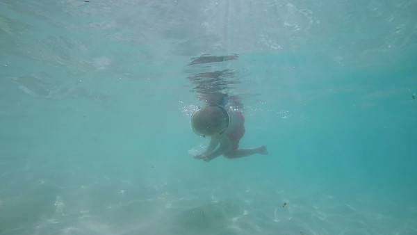 0037 slow motion video of a child spinning and swimming in tropical water