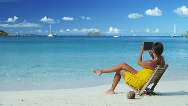 woman taking photo on tablet in teach chair on a tropical beach