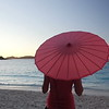 0086 woman walking with umbrella on tropical beach, St John