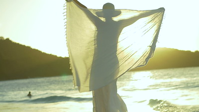 0018 slow motion video of woman twirling sarong on tropical beach at sunset