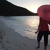 0088 woman walking with umbrella on tropical beach, St John