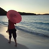 woman walking with umbrella on tropical beach, St John