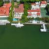 Sideways aerial flight over luxury Miami Beach homes 4k 24p