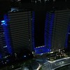 Aerial flyover of a building at night lit in blue Miami Beach 4k