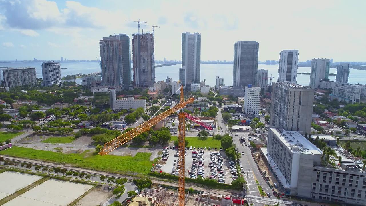 Aerial footage construction cranes crossing