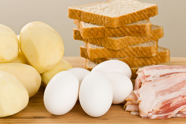 Raw ingredient ready to cook a gourmet meal breakfast. Food on a wooden cutting board. Potato,egg,bacon and whole wheat bread.<br /> <br /> Orientation : horizontal<br /> Concept : cooking, mealtime,morning,