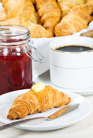 croissant with melted butter on it. Strawberry jam and black coffee in the background. Shallow depth of field.