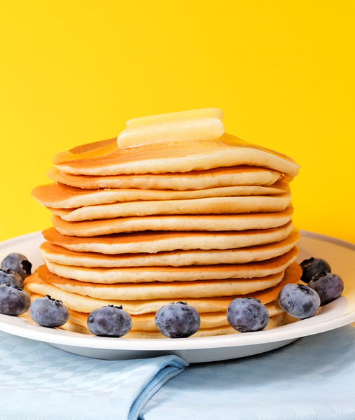 Hot pancake staked with blueberry fruit on a yellow background. Melted butter on the top.