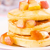 Pancake stacked with maple syrup and apple fruit. Very shallow depth of field.