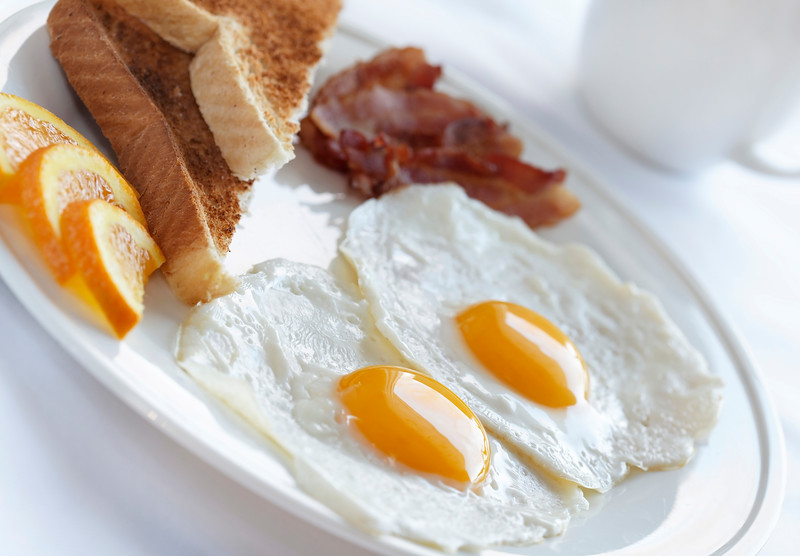 healthy breakfast with egg,bacon and toast on a white plate with very shallow depth of field.
